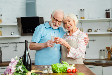 Selective focus of smiling senior couple toasting with champagne by vegetables and flowers on kitchen table