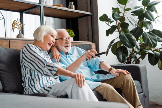 Selective focus of cheerful senior couple watching tv on couch in living room
