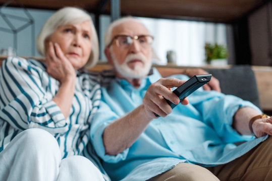 Selective focus of focused senior couple watching tv on couch in living room