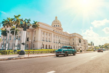 Photo sur Plexiglas Havana vintage American retro car rides on an asphalt road in front of the Capitol in old Havana. Tourist taxi cabriolet.