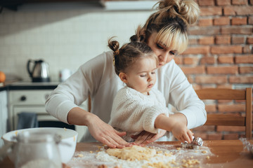 Mother and daughter baking cookies in their kitchen