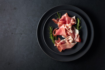 Fototapete - Prosciutto and rosemary on a black plate. Top view.