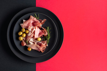 Fototapete - Prosciutto with rosemary and green olives on a black plate. Top view.
