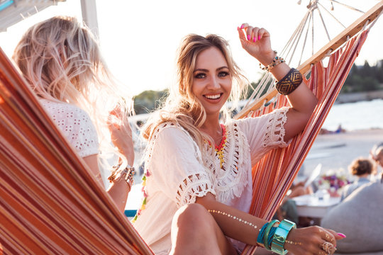 Two young happy beautiful girls dressed boho style white clothes, bracelets sit in hammock at the background sun and ocean