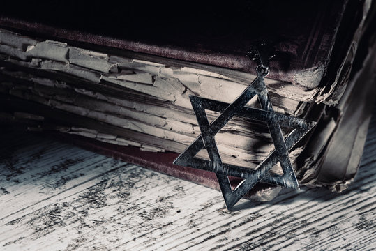 old book and star of david on a rustic surface.