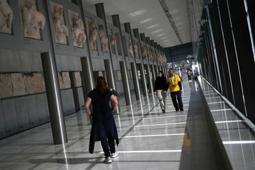 People visit the Parthenon Gallery of the Acropolis Museum, where original sculptures and plaster cast copies of the frieze of the Parthenon temple are exhibited, in Athens