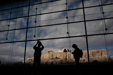 Visitors take pictures of the Parthenon temple seen in the background, as they visit the Parthenon Gallery of the Acropolis Museum, in Athens