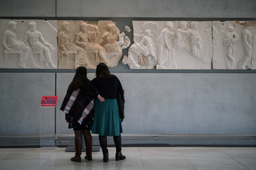 Visitors look at original sculptures and plaster cast copies of the frieze of the Parthenon temple at the Parthenon Gallery of the Acropolis Museum, in Athens