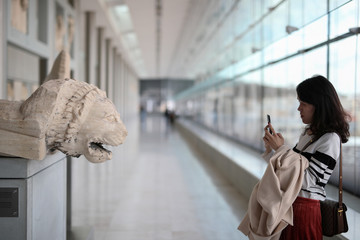 A woman takes a photo as she visits the Parthenon Gallery of the Acropolis Museum, where original sculptures and plaster cast copies of the frieze of the Parthenon temple are exhibited, in Athens