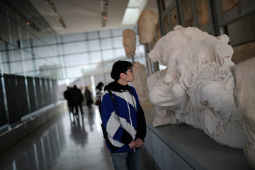 A man visits the Parthenon Gallery of the Acropolis Museum, where original sculptures and plaster cast copies of the frieze of the Parthenon temple are exhibited, in Athens