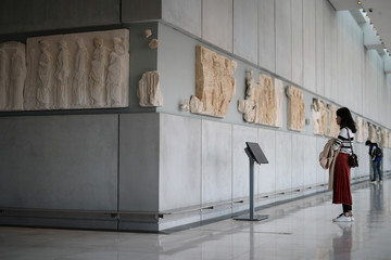 Visitors look at original sculptures and plaster cast copies of the frieze of the Parthenon temple, as they visit the Parthenon Gallery of the Acropolis Museum, in Athens