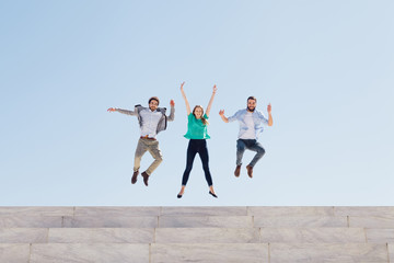 Three friends jump into the air at the top of an external staircase of a building, behind them the blue sky of a spring day - Copy space - Millennial have fun together