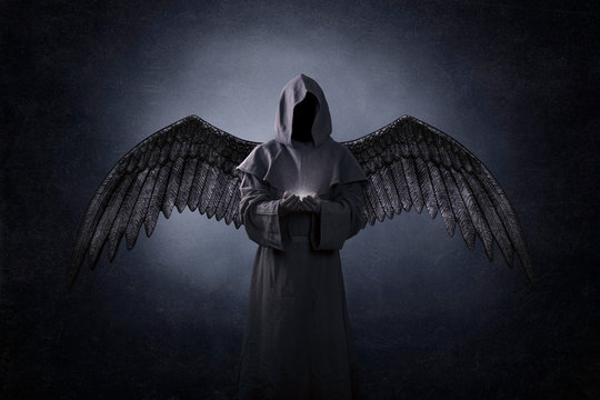 Angel of death with soul in hands in the dark
