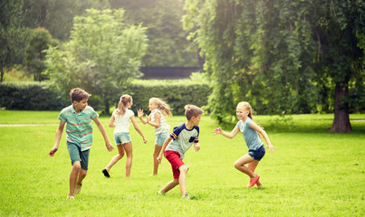 friendship, childhood, leisure and people concept - group of happy kids or friends playing catch-up game and running in summer park Fotobehang