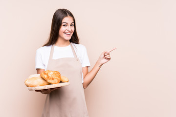 Young caucasian baker woman isolated smiling and pointing aside, showing something at blank space.