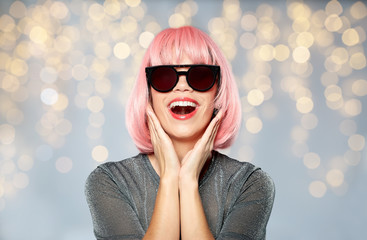 style, fashion and people concept - happy young woman in pink wig and black sunglasses over festive lights background