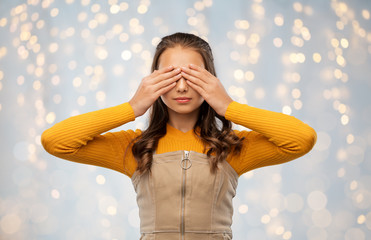 seeing, vision and people concept - teenage girl closing her eyes by hands over festive lights background
