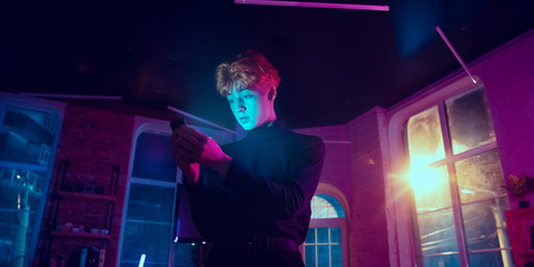 Attented. Cinematic portrait of stylish redhair man in neon lighted interior. Toned like cinema effects in purple-blue. Caucasian model using smartphone in colorful lights indoors. Flyer.