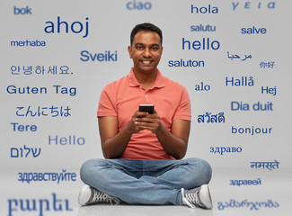 technology, communication and people concept - happy indian man using smartphone over greeting words in different foreign languages on grey background