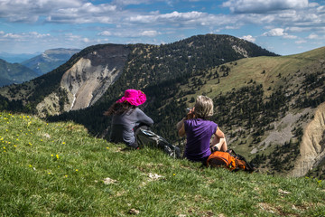 Deux femmes assises contemplant paysage du Dévoluy dans les Hautes -Alpes au printemps