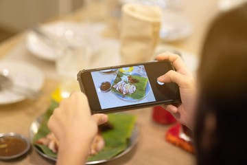 A girl take a picture some food by smartphone in Thai restaurant