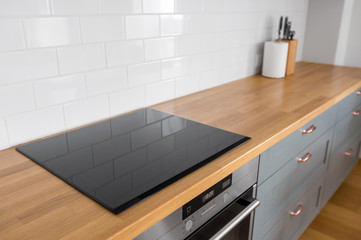 Fototapeta interior and cooking concept - modern kitchen counter with built in oven and electric hob at home obraz