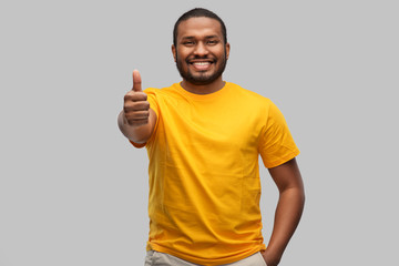 gesture and people concept - smiling young african american man in yellow t-shirt showing thumbs up...