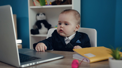 Close up rotation view of serious baby boss sitting in a chair in the office, wearing strict formal suit, looking around and controlling the situation. Miracle, adorable cuteness, happy childhood.