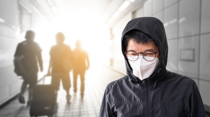 Asian man wearing surgical face mask to prevent flu disease Corona virus and PM 2.5 dust with blurred image of crowded