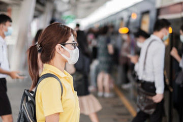 Wall Murals Height scale young Asian woman wearing protection mask against Novel coronavirus (2019-nCoV) or Wuhan coronavirus at public train station,is a contagious virus that causes respiratory infection.Healthcare concept