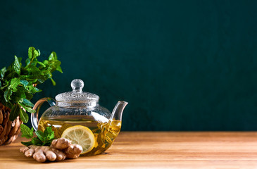 Fresh mint herbal tea in glass teapot, front view background