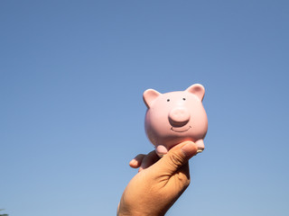 A hands holding pink piggy bank and blue sky background. saving money for retirement fund concept.