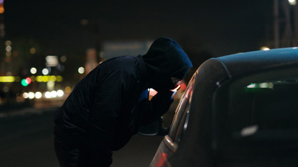 Robber man shines a flashlight in a car stealing at night crime male thief illegal theft stolen danger burglary bandit secure break safety concept money risk insurance checking door slow motion - fototapety na wymiar