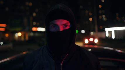 Portrait man bandit in balaclava and hood looking at the camera at night blinking headlights colorful danger dangerous disguise gangster mask robber hooligan portrait terrorist bad mugger