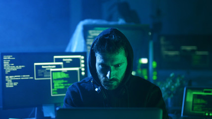 Portrait of insidious hacker organizing virus attack on corporate servers in hideout place. Serious man looking at camera sitting at desk with multiple displays.