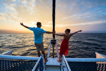 A man and woman stand on a catamaran with outstretched arms at sunset on a cruise off the coast of Maui, Hawaii.