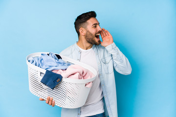 Young handsome man doing laundry isolated shouting and holding palm near opened mouth.