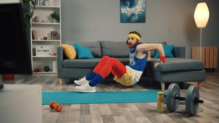 LOS ANGELES, CALIFORNIA, 10 OCTOBER, 2019: Handsome silly sportsman doing exercise leaning on a sofa watching fitness videos at home.
