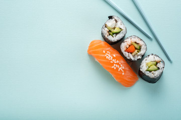 Sushi set with salmon nigiri and roll with cucumber and vegetables with chopsticks on a blue background, for the sushi bar menu