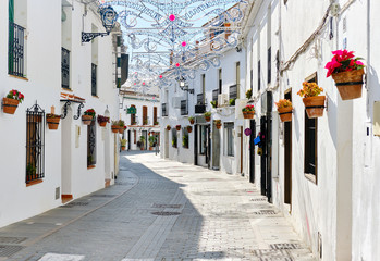 Mijas white washed street, small famous village in Spain. Charming empty narrow streets with New Year decorations, on houses walls hanging flower pots, sunny day no people. Costa del Sol, Málaga