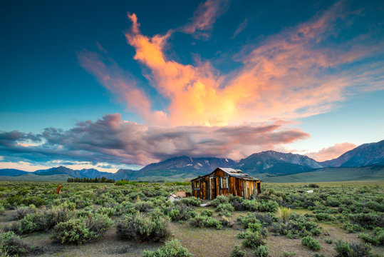 A magnificent sunset explodes over an old abandoned cabin in the desert with the Sierra Nevada mountains in the background near Lee Vining, California.