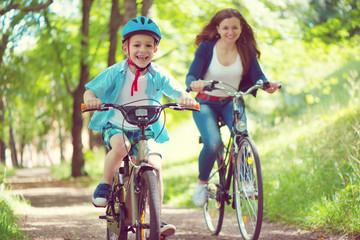 Happy young mother and son ride on bikes in park Fototapete