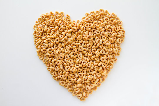 Whole grain oat cereal in a heart shape on a white background, top view. Heart shapes cereal.