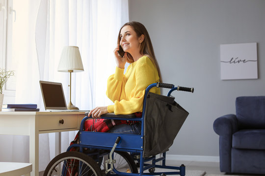 Handicapped young woman in wheelchair talking by phone while using laptop at home