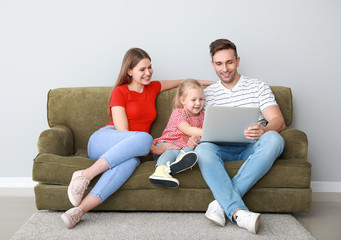 Happy young family with laptop sitting on sofa near light wall
