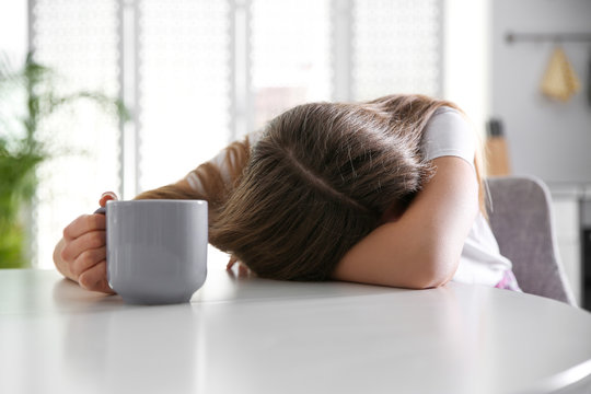 Young woman with cup of drink sleeping at home in morning