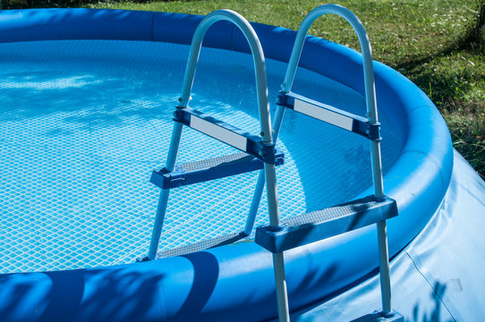 Blue round rubber inflatable family pool detail with ladder closeup