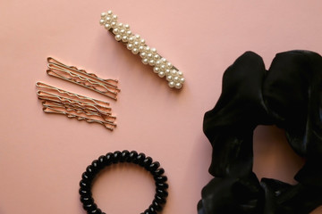 Fashionable hair accessories on pastel pink background; black scrunchie, goldenhair pins, coil hair tie and beret with pearls. Top view. Wall mural