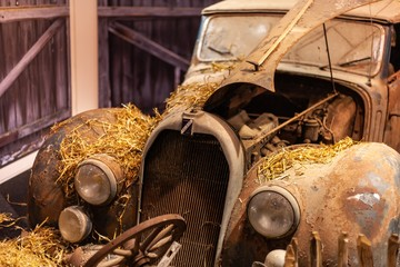 classic rusted car covered in hay in barn