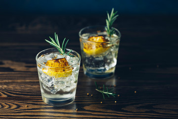 Charred Lemon, Rosemary and Coriander Gin and Tonic is a flavors are perfectly balanced refreshing cocktail. on dark background, close up.